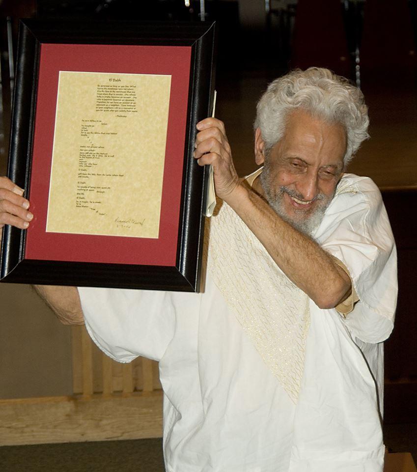 Halim El Dabh holding up a framed poem written by Mwatabu Okantah for his 85th Birthday Gala